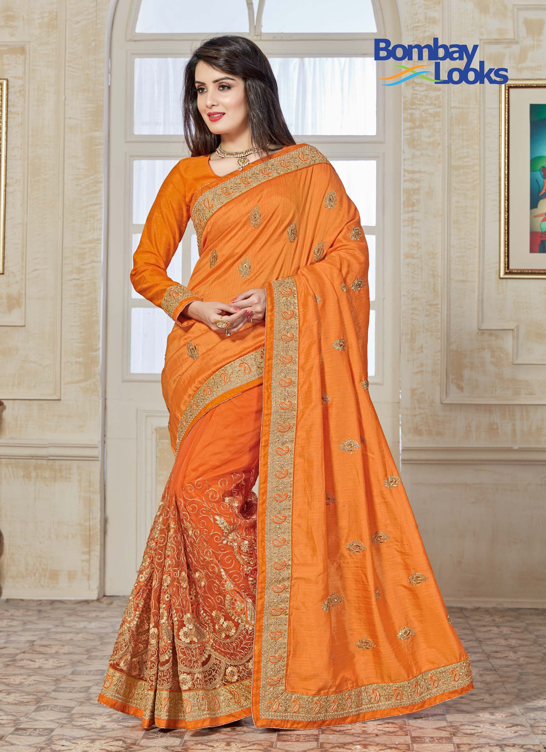 Orange soft and silky net half and half saree with rich golden embroidered skirt